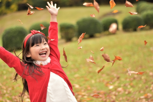 落ち葉で遊ぶ少女