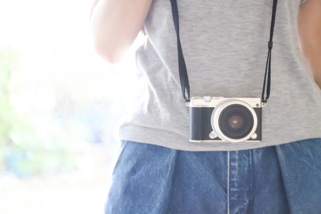 首からカメラを下げる女性