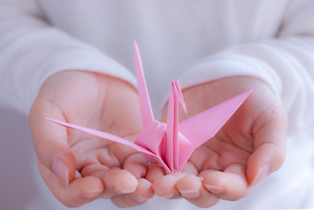 折り鶴を持つ女性