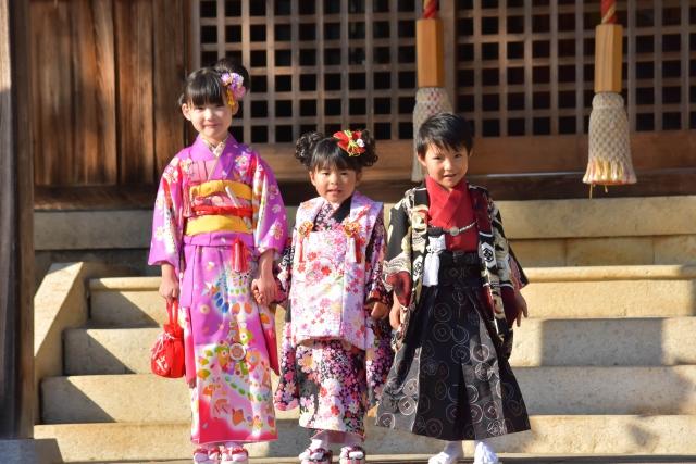 神社の前で手を繋ぐ子供達